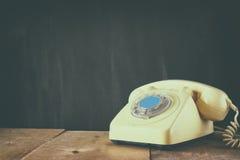 Retro telefon på trätabellen filtrerad bild med urblekt retro stil Fotografering för Bildbyråer