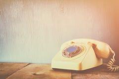 Retro telefon på trätabellen filtrerad bild med urblekt retro stil Arkivfoto