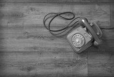 Retro telefon som isoleras på trätabellen arkivbild