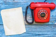 Retro telefono rosso e un foglio di carta per le annotazioni immagine stock