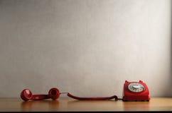 Retro telefono rosso occupato con il ricevitore che trascina attraverso lo scrittorio fotografie stock