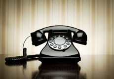 Retro telephone. Vintage telephone over striped wallpaper Royalty Free Stock Image