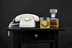 A retro telephone, a bottle and a glass with liquor on a table, Royalty Free Stock Image