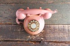 Retro telephone. Pink retro telephone on grey wooden table royalty free stock photo