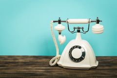 Retro telephone on table in front mint green background royalty free stock photo