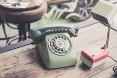 Retro telephone and table lamp on wood table Royalty Free Stock Image