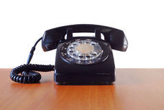 Retro telephone. Vintage black telephone on wooden desk royalty free stock photo