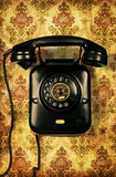 Retro telephone on vintage wallpaper Royalty Free Stock Photos