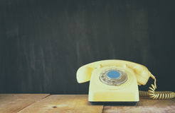 Retro telephone on wooden table. filtered image with faded retro style Stock Image