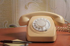 Retro telephone on wooden table in front gradient background Stock Photos