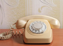 Retro telephone on wooden table in front gradient background.  Royalty Free Stock Image