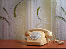 Retro telephone on wooden table in front gradient background.  Royalty Free Stock Photo