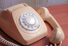 Retro telephone on wooden table in front gradient background.  Stock Photo