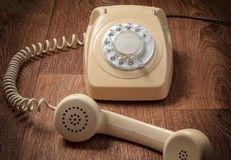 Retro telephone on wooden table in front gradient background Royalty Free Stock Photos
