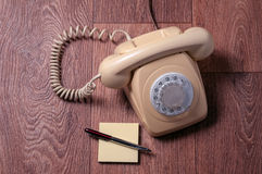 Retro telephone on wooden table in front gradient background Stock Image
