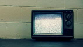 Retro Television & Static. Old generic tv with static sitting on floor against an industrial block wall. Shot on HD 1080p stock video