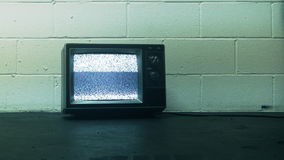 Retro Television & Static. Old generic tv with static sitting on floor against an industrial block wall. Shot on HD 1080p stock footage
