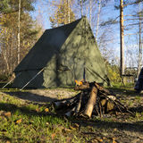 Retro tent in forest and camp fire. In the wild forest in autumn season Stock Image