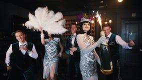 Retro themapartij - Jongeren die pret en het dansen hebben - een vrouw die een reusachtige fles champagne met vuurwerk houden stock video