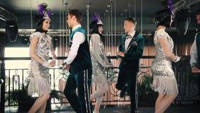 Retro themapartij - Jongeren in glinsterende retro kleren die op de vloer dansen stock videobeelden