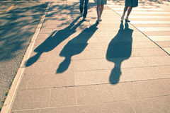 Retro three people shadows on sunny city street. Vintage color people shadows walking on city street on hot summer sunny day. People walking down the street Royalty Free Stock Photos