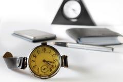 Retro timmar mot bakgrunden av den moderna telefonen Arkivbilder