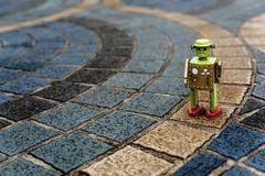Retro tin robot toy standing on ground with pattern Concept Stock Photo