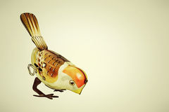 Retro tin toy bird on a retro background. Retro styled image of a tin wind up toy bird on a vintage background Stock Images