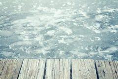 Retro tonad gammal träpir på is, utrymme för text Arkivfoto