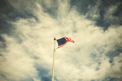 Retro toned American flag on the cloudy sky Royalty Free Stock Photo