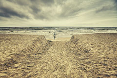 Retro toned beach with rainy clouds. Stock Images