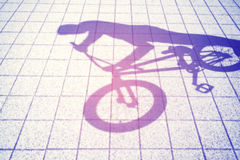 Retro toned blurred shadow of a teenager riding a bmx bike Stock Photos