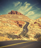Retro toned curved desert highway. Royalty Free Stock Photo