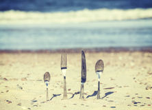 Retro toned cutlery stuck in sand on the beach. Royalty Free Stock Photos