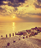 Retro toned dramatic sunset over beach and rocky pier Royalty Free Stock Image