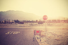 Retro toned empty shopping trolley left on street at sunset. Royalty Free Stock Photo