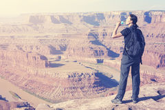 Retro toned female tourist drinking water by canyon. Stock Images