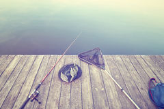 Retro toned fishing equipment on a wooden pier. Stock Photos
