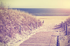 Retro toned photo of a beach path, old film style. Royalty Free Stock Photo