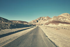 Retro toned picture of a desert road in Death Valley, USA. Stock Photo