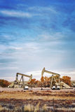 Retro toned picture of two oil pumps. Stock Photography