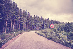 Retro toned road with speed limit sign Royalty Free Stock Photo