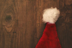 Retro toned Santa Claus hat on wooden desk Royalty Free Stock Photo