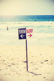 Retro Toned Swim And Surf Sign On The Beach. Stock Photo