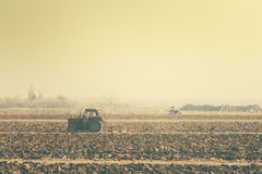 Retro toned tractors on arable field Royalty Free Stock Image
