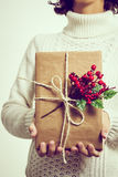 Retro toned woman gives a Christmas gift Royalty Free Stock Photography