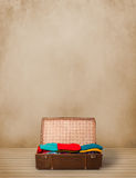 Retro tourist luggage with colorful clothes and copyspace Royalty Free Stock Images