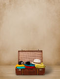 Retro tourist luggage with colorful clothes and copyspace Stock Image