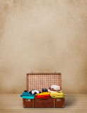 Retro tourist luggage with colorful clothes and copyspace Stock Photography