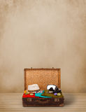 Retro tourist luggage with colorful clothes and copyspace Stock Photos